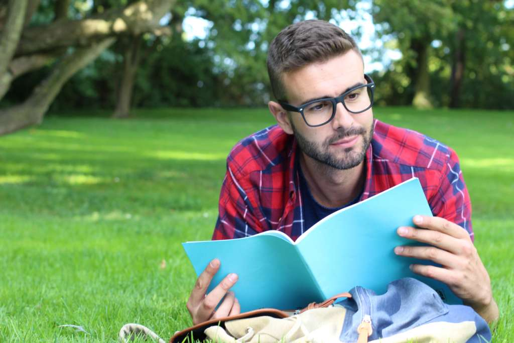 Cheerful student reading in the park
